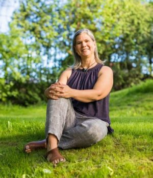 Image of Janet Smylie sitting on green grass.